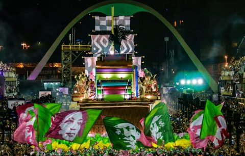Imagem da Sapucaí durante o desfile da Mangueira, varias bandeiras com o rosto de ícones da resistência popular brasileira estampados