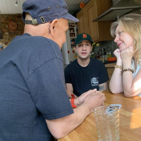 Sue, Morgan e um homem branco de boné e camiseta azul, sentados conversando em uma mesa