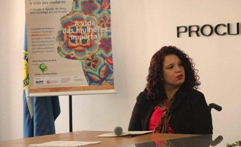 """Elisandra Carolina dos Santos, mulher parda de cabelo cacheado, sentada diante de uma mesa olhando para o lado. Á sua direita tem um bainner escrito """"A vida das mulheres importa!""""."""