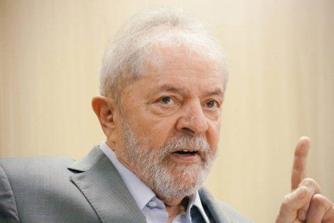 Ex-presidente Lula - homem idoso branco, vestindo terno cinza- sentado, falando com uma das mãos levantadas