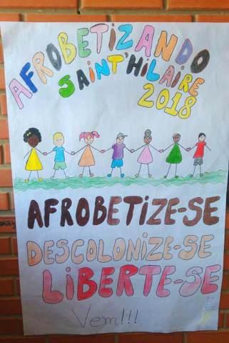 """Cartaz feito á mão, escrito com letras coloridas a frase: """"Afrobetizando Jaint'hilaire 2018. Afrobetize-se, Descolonize-se, Liberte-se, Vem !!"""". A também um desenho de varias crianças de etnias diferentes de mãos dadas."""