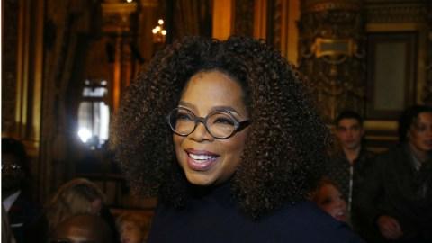 Oprah Winfrey- mulher negra de cabelo cacheado e volumos ,usando oculos- sorrindo