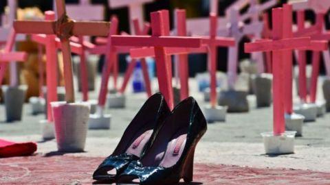 Varias cruzes em pé simbolizando lapides de mulheres mortas. a frente deles um par de salto alto preto.