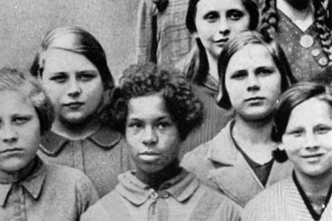 Fotografia antiga em preto e branco,tirada na Alemanha nazista, de uma garota negra vestindo uniforme escolar. Diferentemente das colegas brancas que encaram a câmera, ela desvia o olhar.