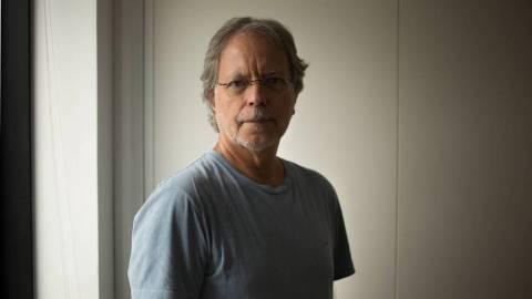 Mia Couto- homem branco de cabelos brancos, usando óculos, vestindo uma camiseta cinza,- em pé