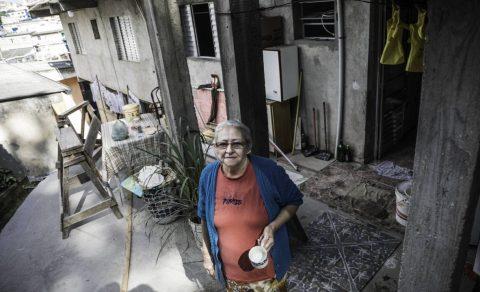 Nailda Mendes de Moraes Silva - mulher idosa branca, com uma caneca de porcelana branca na mão, vestindo camiseta vermelha e um casaco azul- em pé na frete de uma casa simples