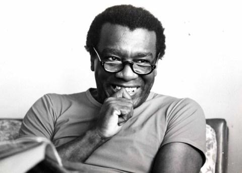 Foto em preto e branco de Milton Santos, homem negro usando óculos, sentado sorrindo com um livro na mão