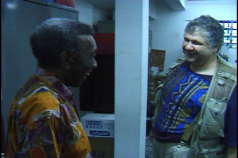 Milton, vestindo uma camiseta estampada amarela, em pé com Silvio Tendler, homem branco vestindo camiseta estampada azul com amarelo e um colete por cima, em pé conversando