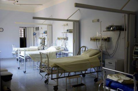 Foto de um quarto de hospital, com equipamentos hospitalar e camas vazias.