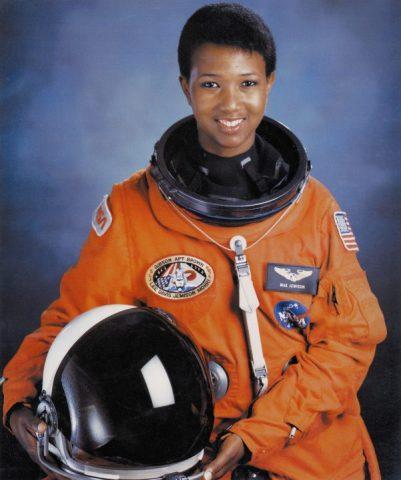 Mae Jemison, mulher negra de cabelo curto, em pé vestindo roupa de astronauta laranja e com o capacete na mão