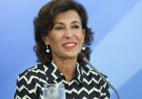 Maria Silvia Bastos Marques, mulher idosa branca, vestindo camiseta estampada preta e branca, sentada sorrindo