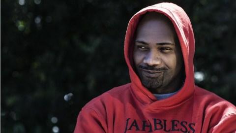 MV Bill- homem negro, vestindo moletom vermelho com o gorro do moletom na cabeça- sentado de braços cruzados e dando um ligeiro sorriso.