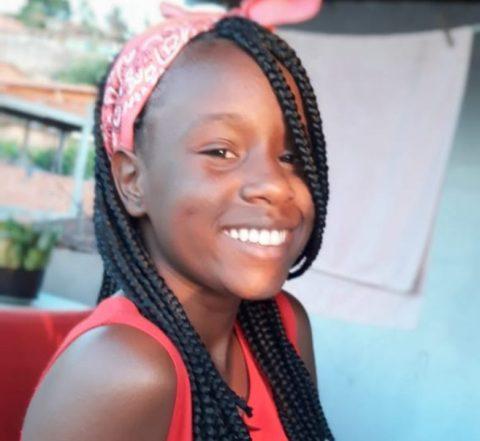 Quézia Ferreira, jovem negra de tranças, com uma bandana vermelha na cabeça, sentada sorrindo.