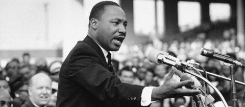 For em preto e branco de Martin Luther King, homem negro com pouco cabelo, vestindo terno, em pé na frente de microfones descurando.