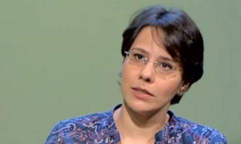 Juliana Doretto, mulher branca de cabelo curto, usando óculos de grau e vestido estampado colorido, sentada durante uma entrevista.