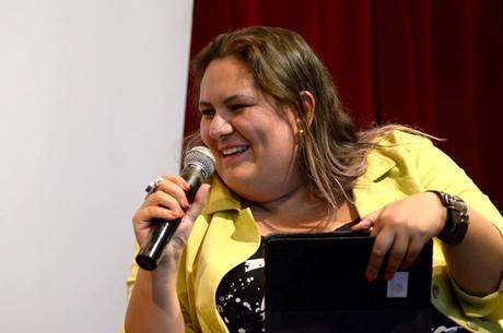 Jéssica Balbino- mulher branca de cabelo loiro que vai na altura dos ombros, vestindo um blazer amarelo- sentada sorrindo com um microfone na mão direita e uma pasta na mão esquerda.