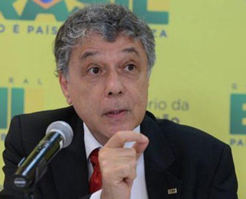 Chico Soares - homem branco de cabelos grisalhos, vestindo terno preto gravata vermelha- sentado falando em frente á um microfone