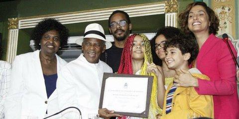 Antônio Pitanga - homem idoso negro, vestindo roupa branca e chapéu branco com uma faixa preta- recebendo a homenagem ao lado da esposa Benedita da Silva, os filhos Rocco e Camila Pitanga e as três netas
