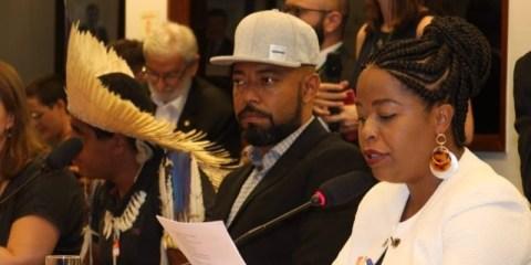 Silvia Souza- mulher negra de cabelo trançado, vestindo jaqueta branca- lendo um documento ao lado de Douglas Belchior- homem negro, vestindo palitó e boné cinza