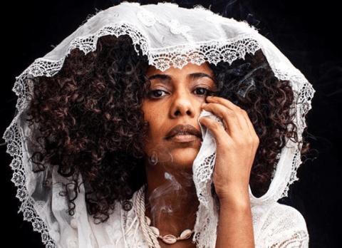 Naruna Costa - mulher negra de cabelo cacheado, com um capuz branco na cabeça- olhando para frente com a mão esquerda no rosto