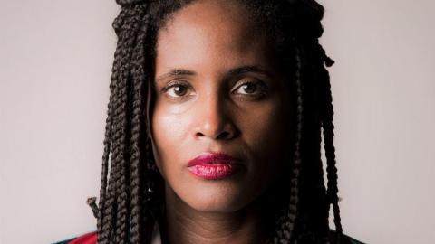 Foto com foco no rosto de Djamila Ribeiro, mulher negra de tranças, usando batom rosa claro