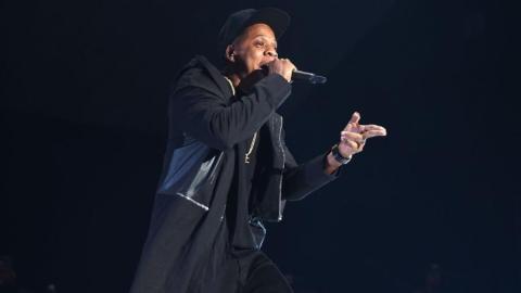 Foto de Jay-Z - homem negro, usando calça,camiseta e jaqueta preta- cantando durante um show