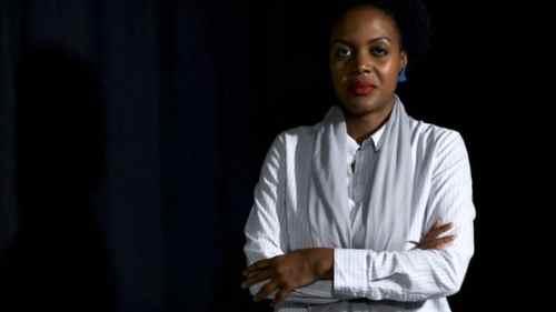 Joacine Katar Moreira- mulher negra de cabelo curto, usando roupa branca, brinco azul e batom vermelho- em pé com os braços cruzados