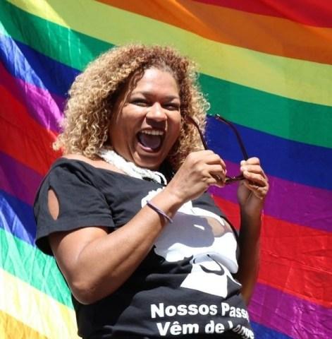 Rivânia Rodrigues- mulher negra, de cabelo cacheado loiro- sorrindo, segurando um óculos. Ao fundo uma bandeira LGBTI estendida