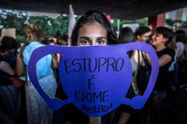 """Todo de uma mulher com um cartaz na frente do rosto escrito """"Estupro é crime, Juntas!"""""""