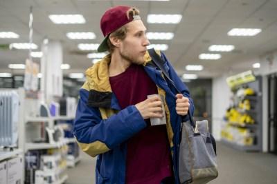 Foto de um homem branco roubando um produto no mercado e escondendo dentro da jaqueta