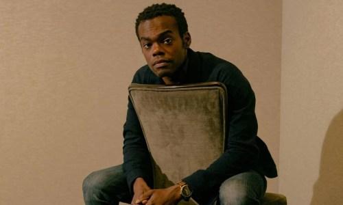 William Jackson Harper- homem negro, com pouco cabelo, vestindo camiseta verde musgo e calça jeans- sentado em uma cadeira