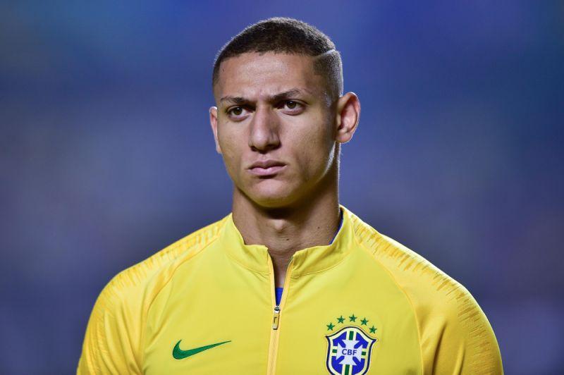 Richarlison- homem pardo vestindo o uniforme da seleção Brasileira- em pé olhando para frente