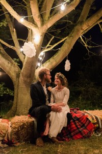 Bride and groom under a tree with fairy lights at night