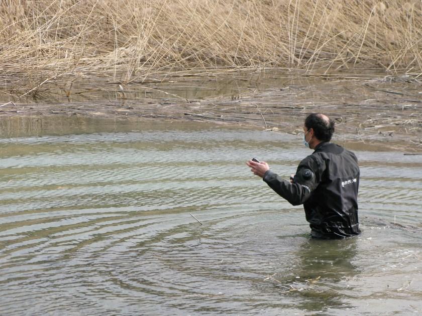 Daniel entrando a la laguna con el GPS en la mano y el agua por la cuintura.