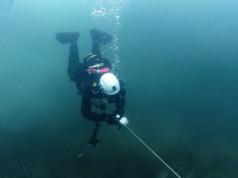 Buceador extendiendo un cabo bajo el agua para montar un transecto de control subacuático.