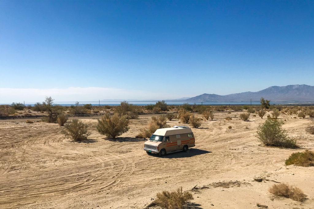 Camper van in the desert of California with Salton Sea