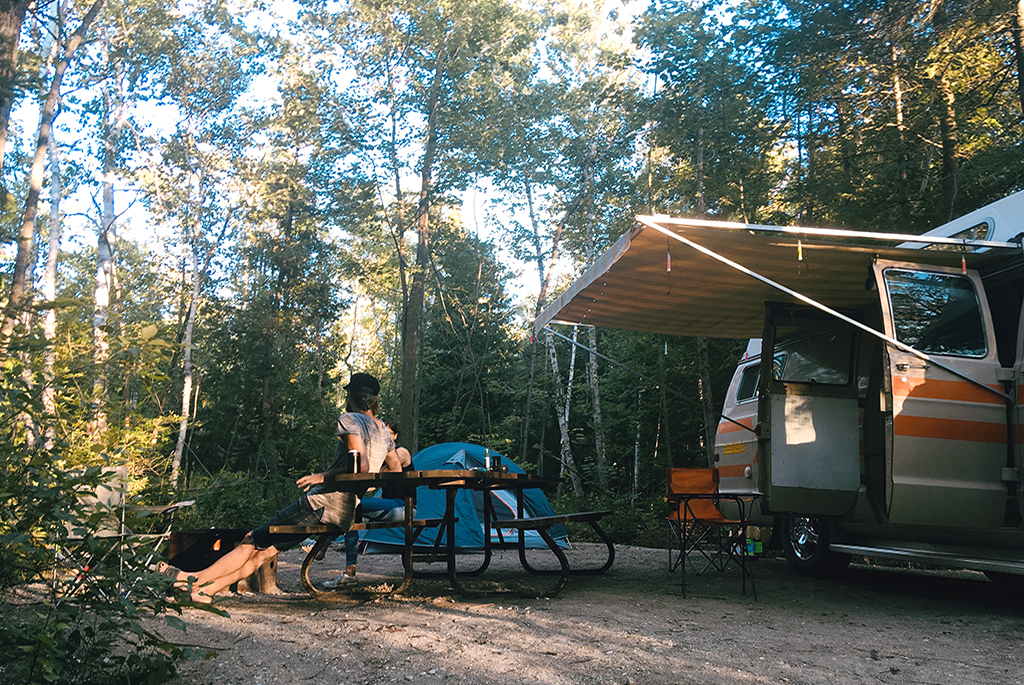 Man sitting at picnic table with camper van and tent set up at a campsite in the woods
