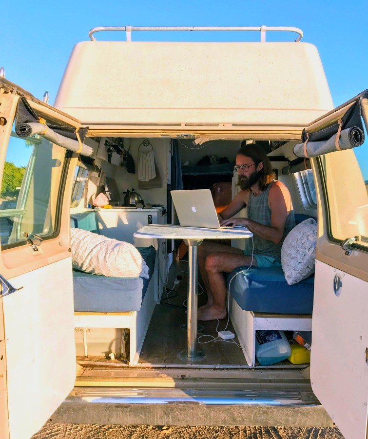 Man sitting at a table with a laptop in the back of a camper van