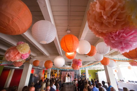 A bride and groom facing each other at the altar during the wedding ceremony at 78TH STREET Studio in Cleveland, Ohio decorated with white and orange paper lanterns and paper flowers hanging from the ceiling.