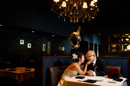 An image of a bride and groom sitting down in a booth at 91 Wood Fired Oven where the bride is wearing a strapless dress and a flower in her updo leaning in towards the groom with her hand touching his chin while the groom is wearing his tuxedo and glasses with a gold chandelier and gold decorations set inside a dark blue room.