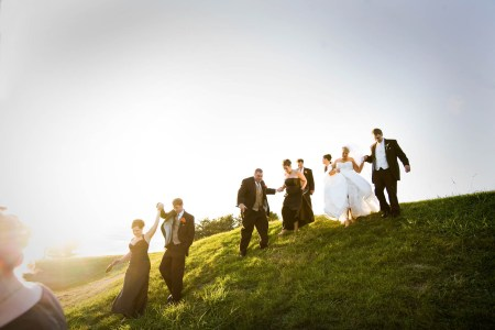 A picture of a bride and groom with their wedding party trying to walk down a green grassy hill where the bride and groom are in the top right corner holding hands and the rest of the party is spread out toward the left of the photo and the sun is setting on the left casting a beautiful glow over everything under a white sky in Dover.