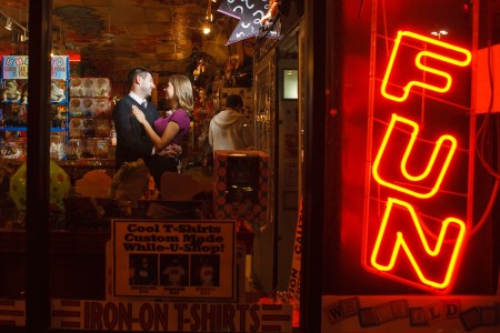 A picture of an engaged couple standing just to the left of the center of the photo facing each other in an embrace while standing in the middle of the Big Fun Toy Store full of trinkets and brightly colored toys shot through the glass window front at night where a sign with the word FUN is light up in red in the right side of the photo.