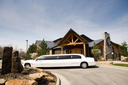 A photo taken from the circular cement driveway facing the brown wood with stone chimney and wooden beamed building of Blue Canyon Kitchen and Tavern in Twinsburg on a bright blue sky day with a white stretch limo in the center of the photo.