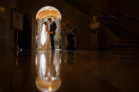 A bride and groom are standing backlit in front of an arched doorway facing each other holding hands in a darkened marbled floored room of the Cleveland Public Library where the doorway has an ornate metal grated hinged door.