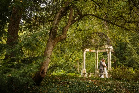 An image of a groom in a grey tuxedo is holding his bride in her white gown from behind while standing under a garden arbor with a wrought iron domed roof with white pillars surrounded by a forest of green foliage at the club at Hillbrook in Ohio.