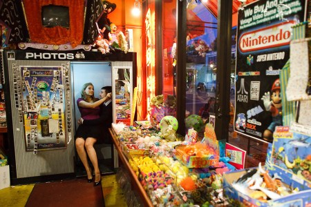 An image of an engaged couple where the woman is wearing a black skirt and purple top looking directly at the camera while sitting on the man's lap who is in a dark suit inside a photo booth which is part of an eclectic store full of bright colored trinket toys sitting on a table all in the right of the photo .
