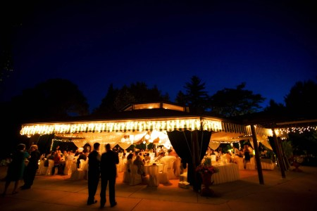 An evening photo taken at dusk of the outdoor tented space at Delucas Place where the reception tables and chairs are covered in white linen and the tent awnings are lit up with golden yellow lights and the guests are mingling in the chais and standing on the cement ground where the sky in the background is a stunning deep blue color.