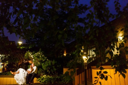 An outdoor evening picture of a bride leaning back into her groom's arms while they are sitting on a low wooden wall surrounded by green foliage on the walkway lit with soft yellow lights with a deep blue skyline and dark green leaves at a Doubletree hotel.