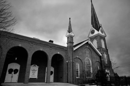A black and white image of the outside of the brick Federated Church in Ohio with arched entry ways and two steeples on a dark and stormy day with bare trees and shrubs.