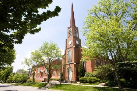 An image of a quaint red brick First Congregational Church in Hudson, Ohio with an arched white door under a tall steeple taken from the corner of the building where the church sits on the lower right half of the photo and the steeple extends up towards the top under a blue sky with tall green trees on either side of the photo.